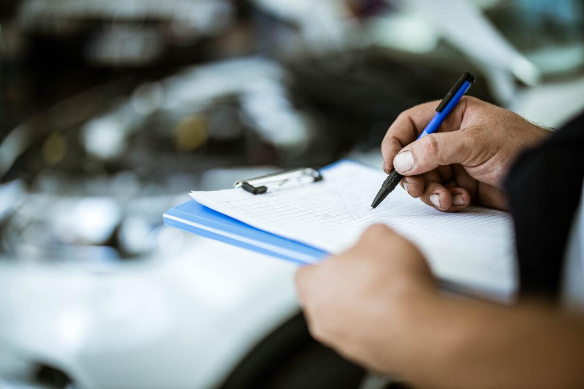 Close up of unrecognizable auto mechanic going through checklist.